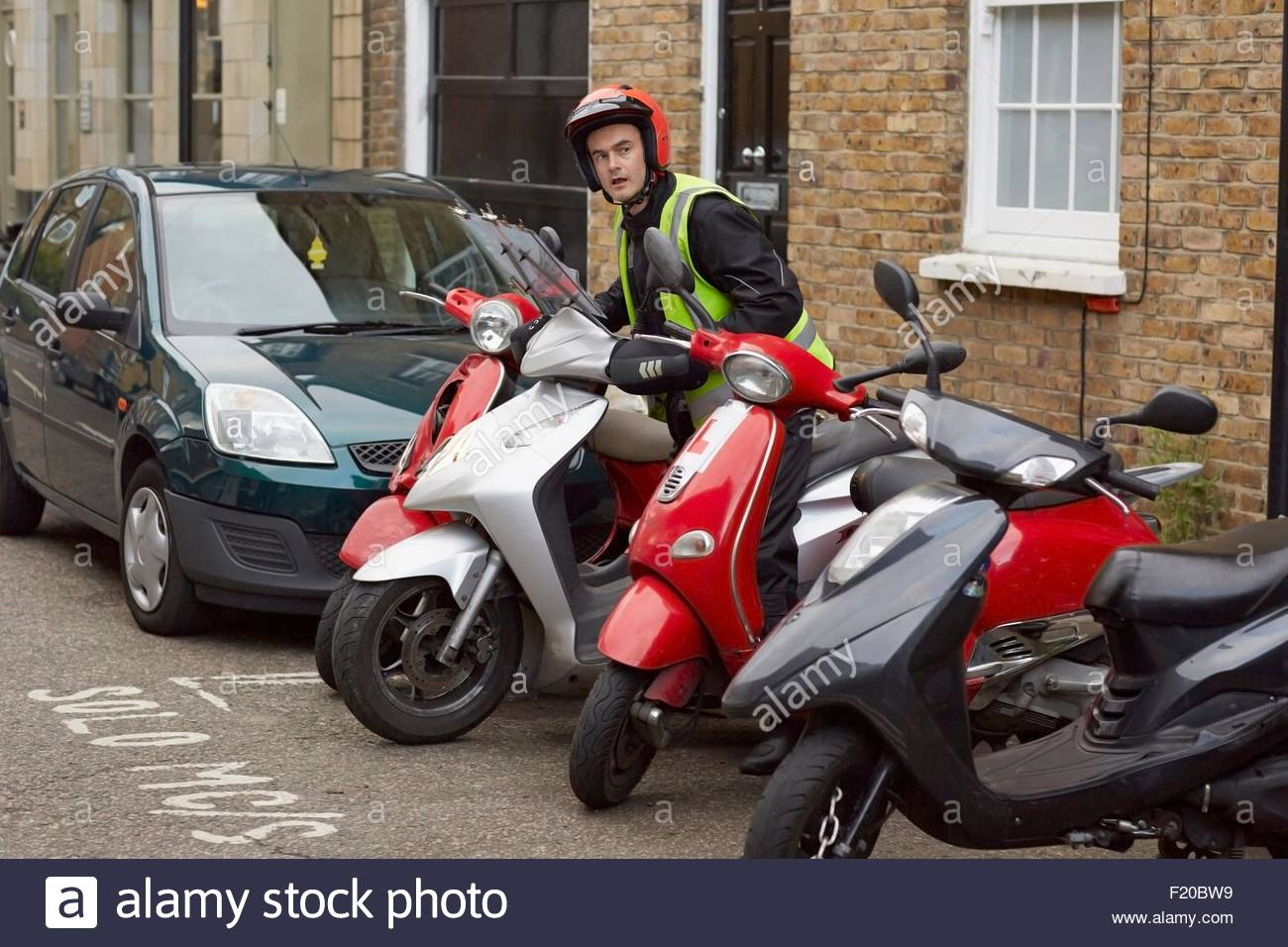 Motor scooter rider parking on street - Stock Image