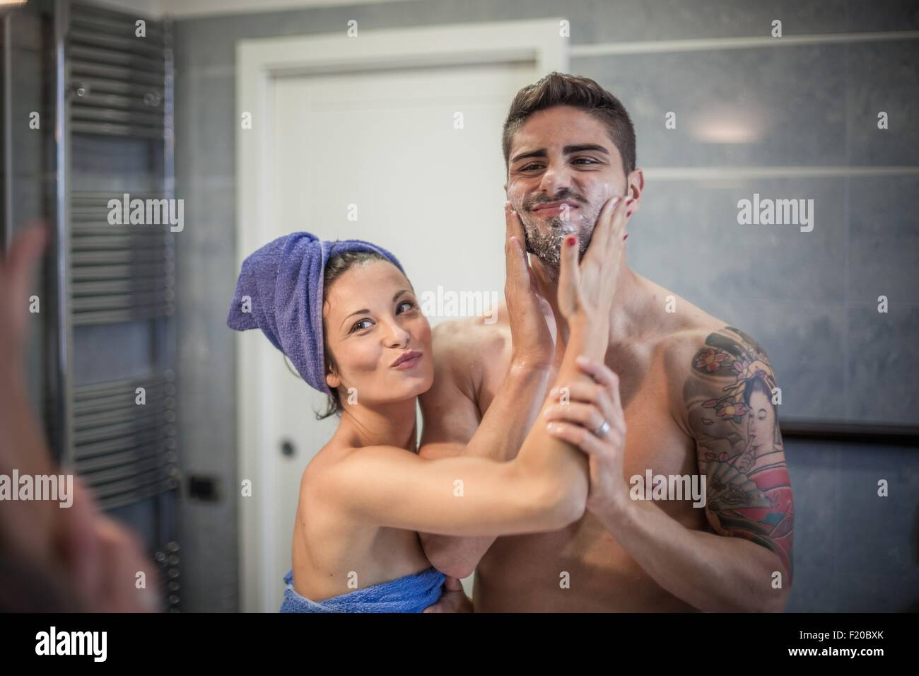 Bathroom mirror image of young woman applying shaving lotion to boyfriends cheeks - Stock Image