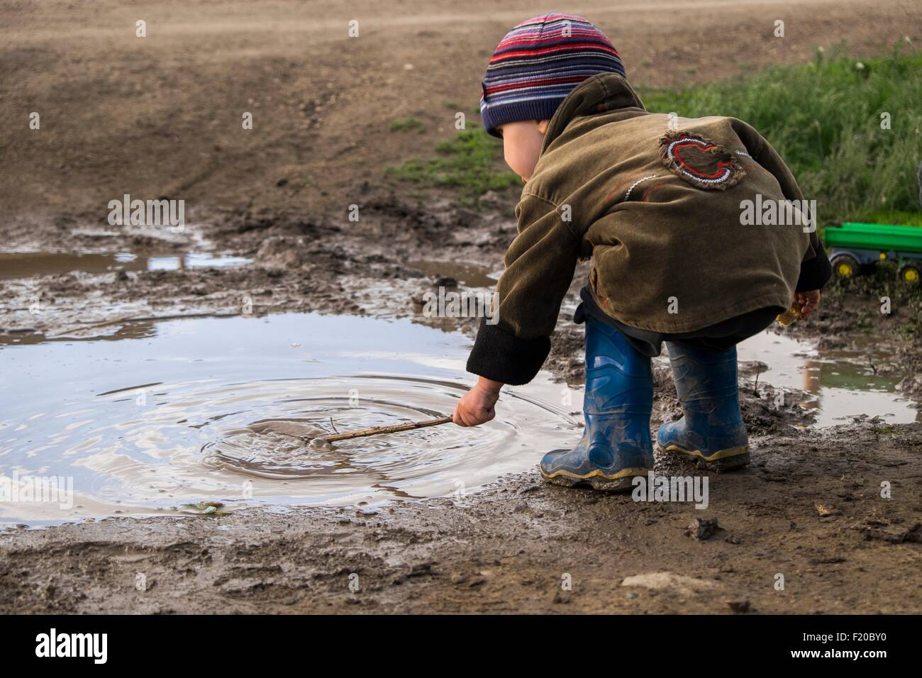 Male toddler wearing rubber boots playing with stick in puddle Stock Photo