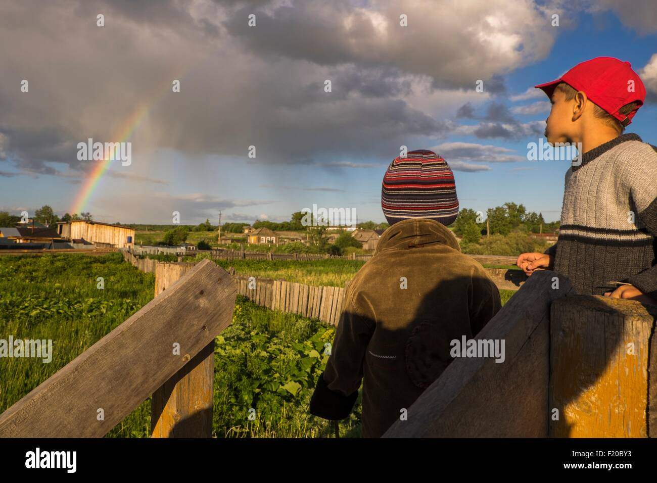 Two brothers gazing at rainbow from field - Stock Image