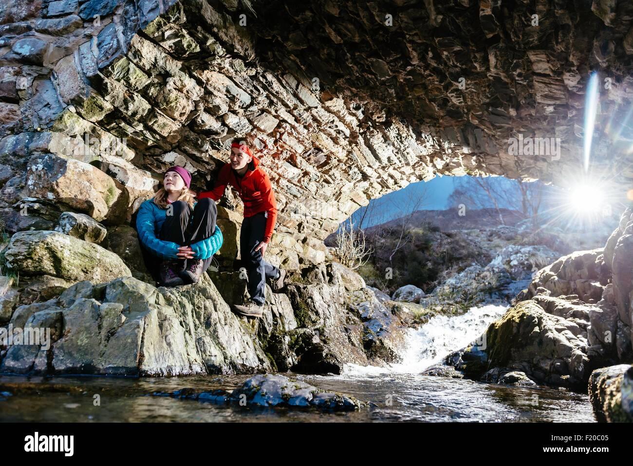 Young couple hiking, resting under bridge, Ashness Bridge, Keswick, Lake District, Cumbria, United Kingdom - Stock Image