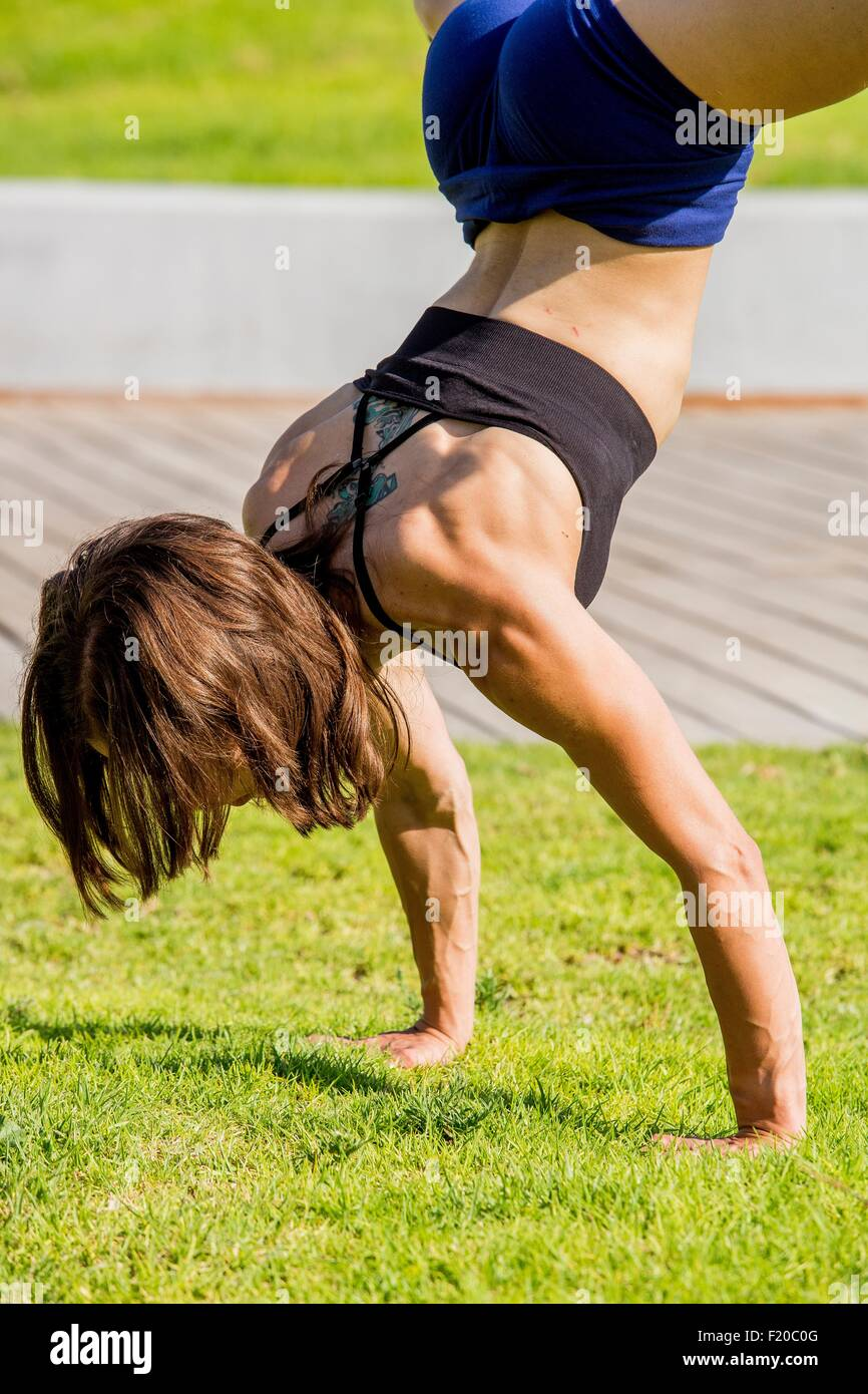 Young woman doing handstand in park - Stock Image
