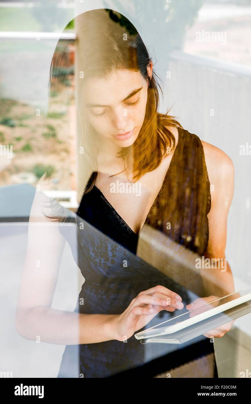 Young woman using digital tablet, photographed through glass - Stock Image