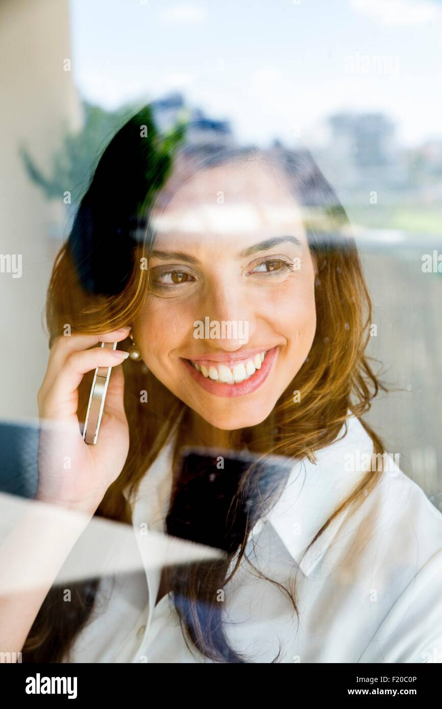 Young woman using smartphone, smiling, photographed through glass - Stock Image