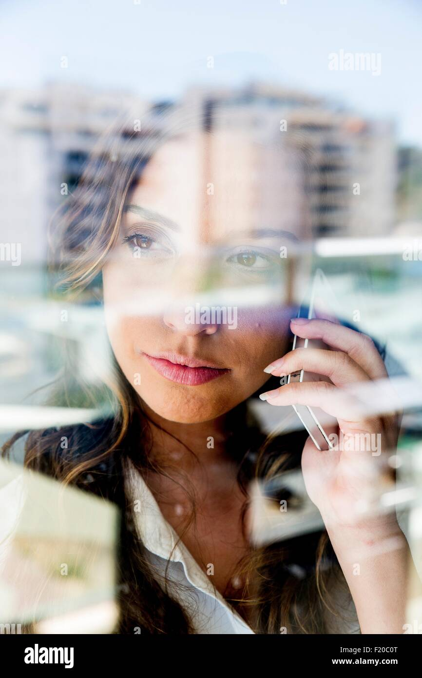 Young woman using smartphone, pensive expression, photographed through glass - Stock Image