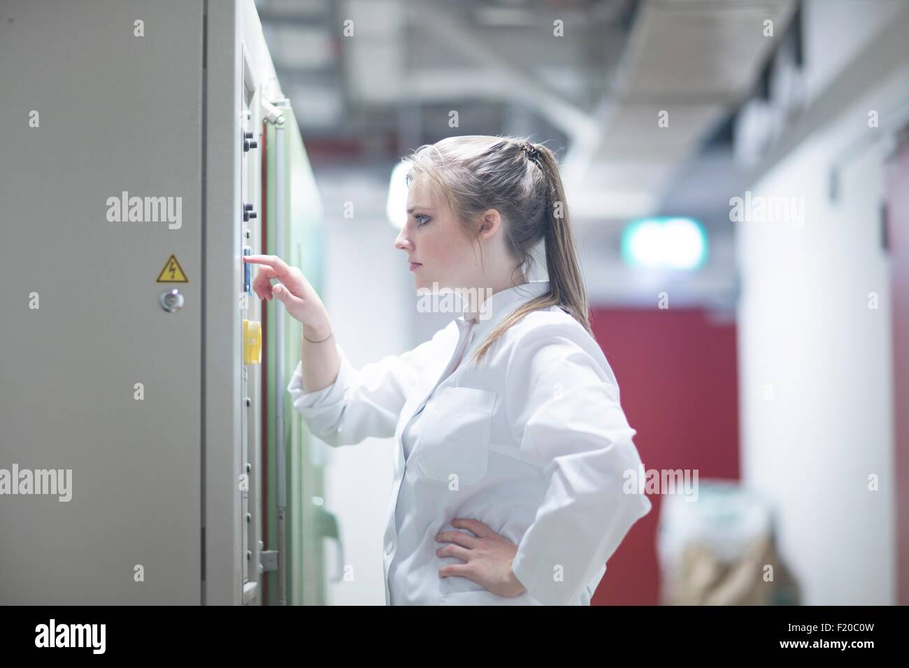 Young female scientist pressing button in technical room - Stock Image