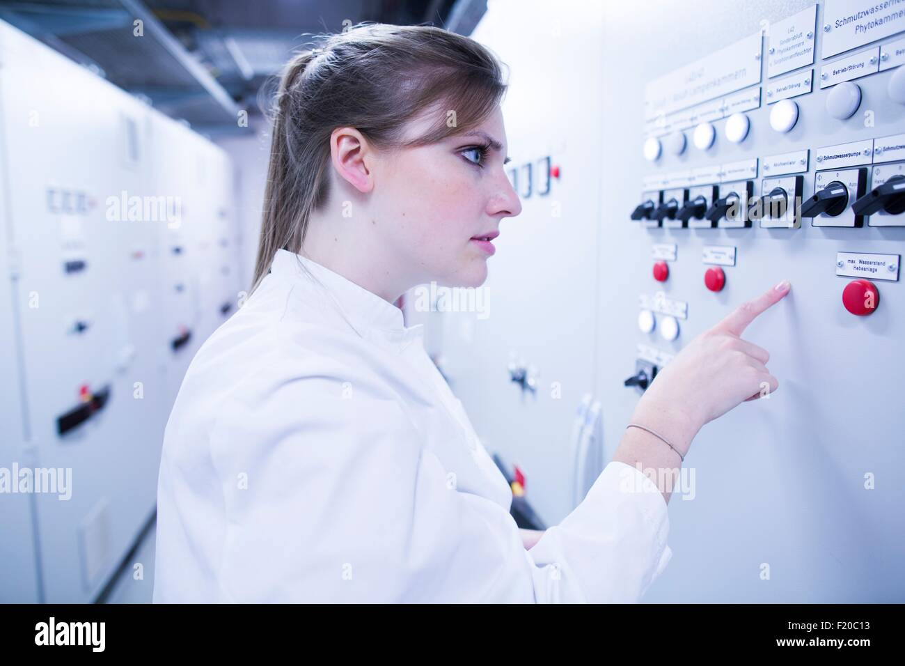 Young female scientist pointing at machine in technical room - Stock Image