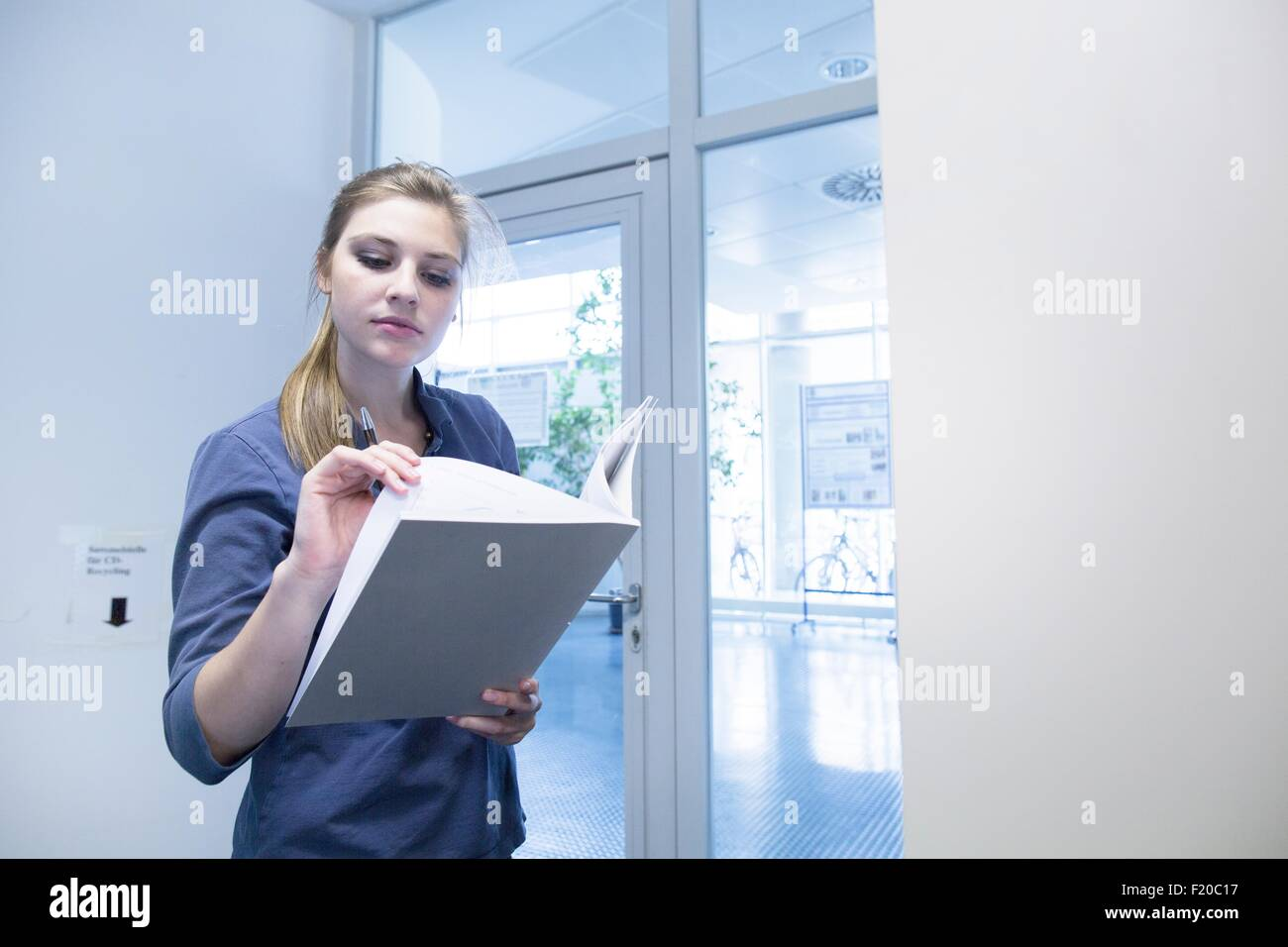 Young female student reading textbook in library - Stock Image
