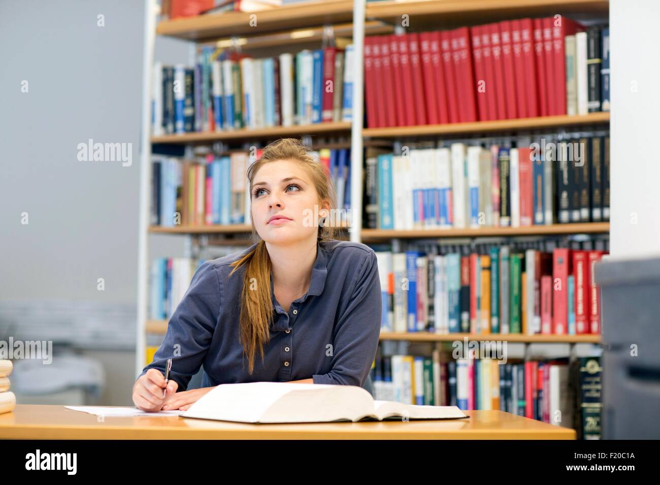 Young female student reading textbook gazing up from library desk - Stock Image