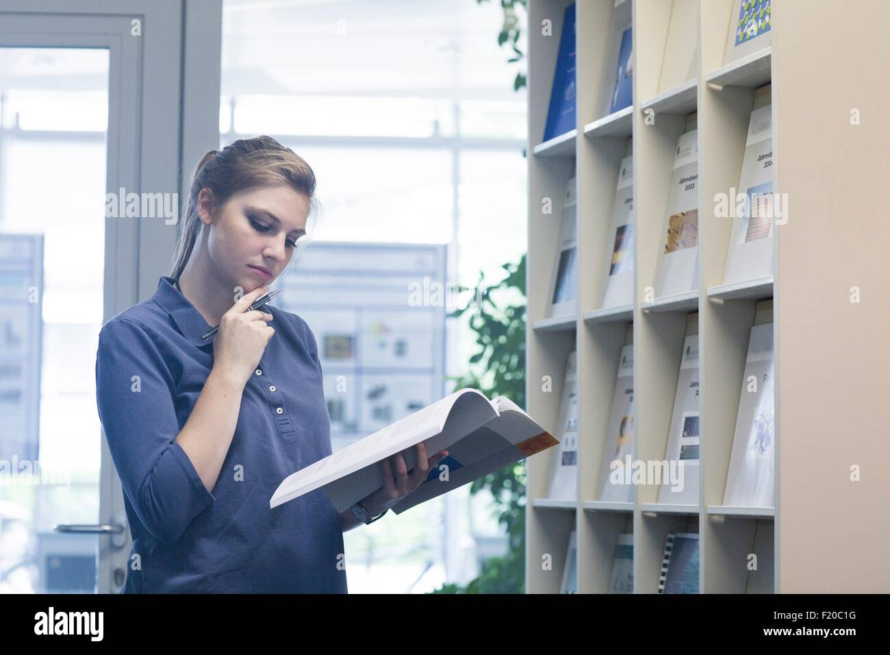 Young female student with hand on chin reading textbook in library - Stock Image