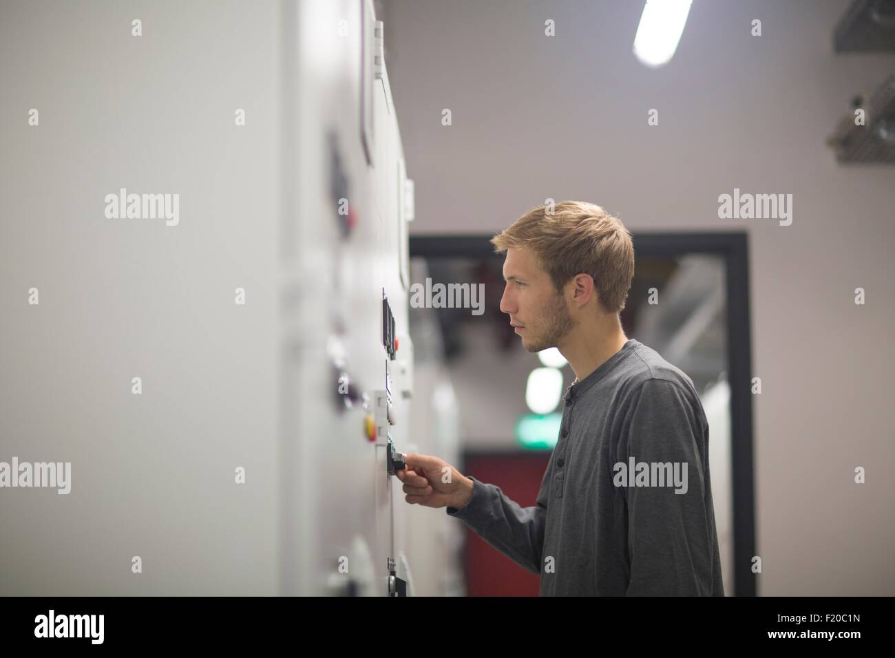 Young male technician turning switch in technical room - Stock Image