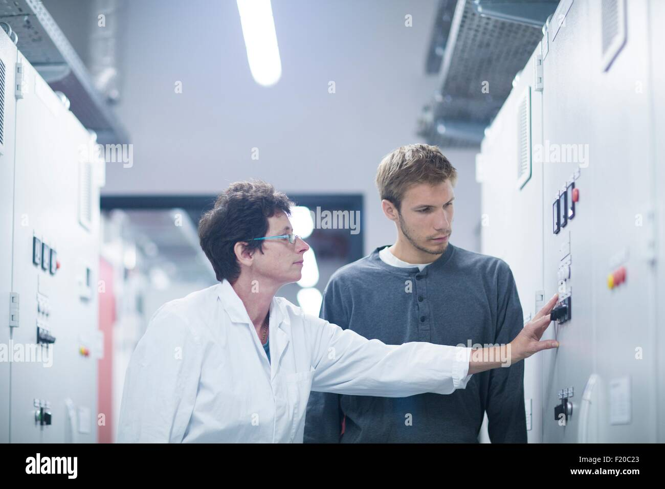Scientist and technician pressing switch in technical room - Stock Image
