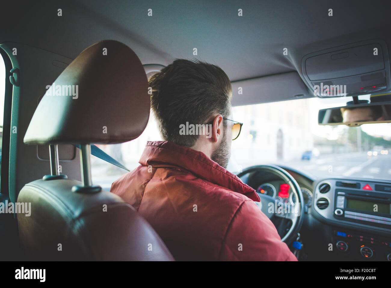 Rear view of young man on the road driving car - Stock Image