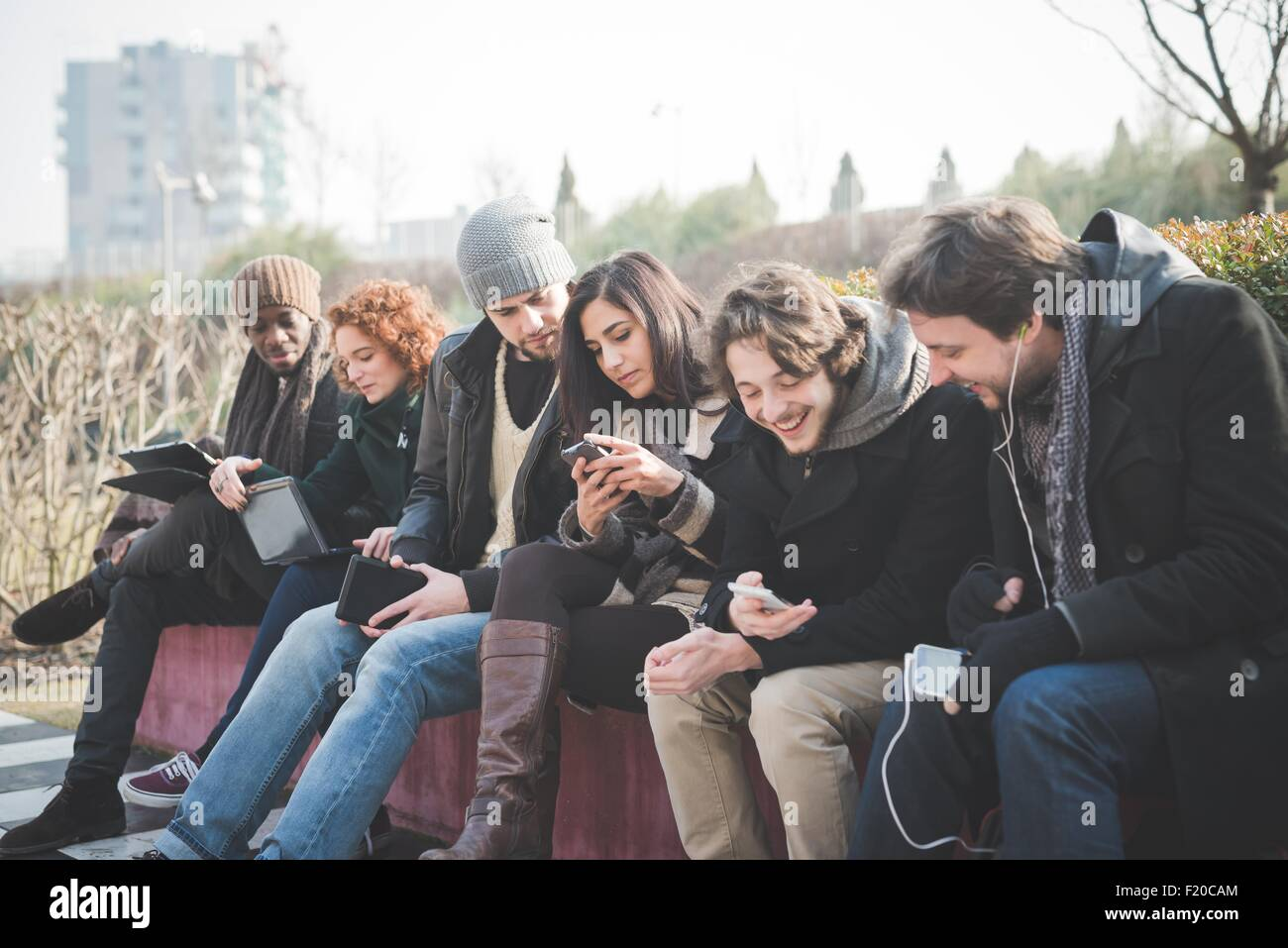 Six young adult friends networking on smartphones and digital tablets in park - Stock Image