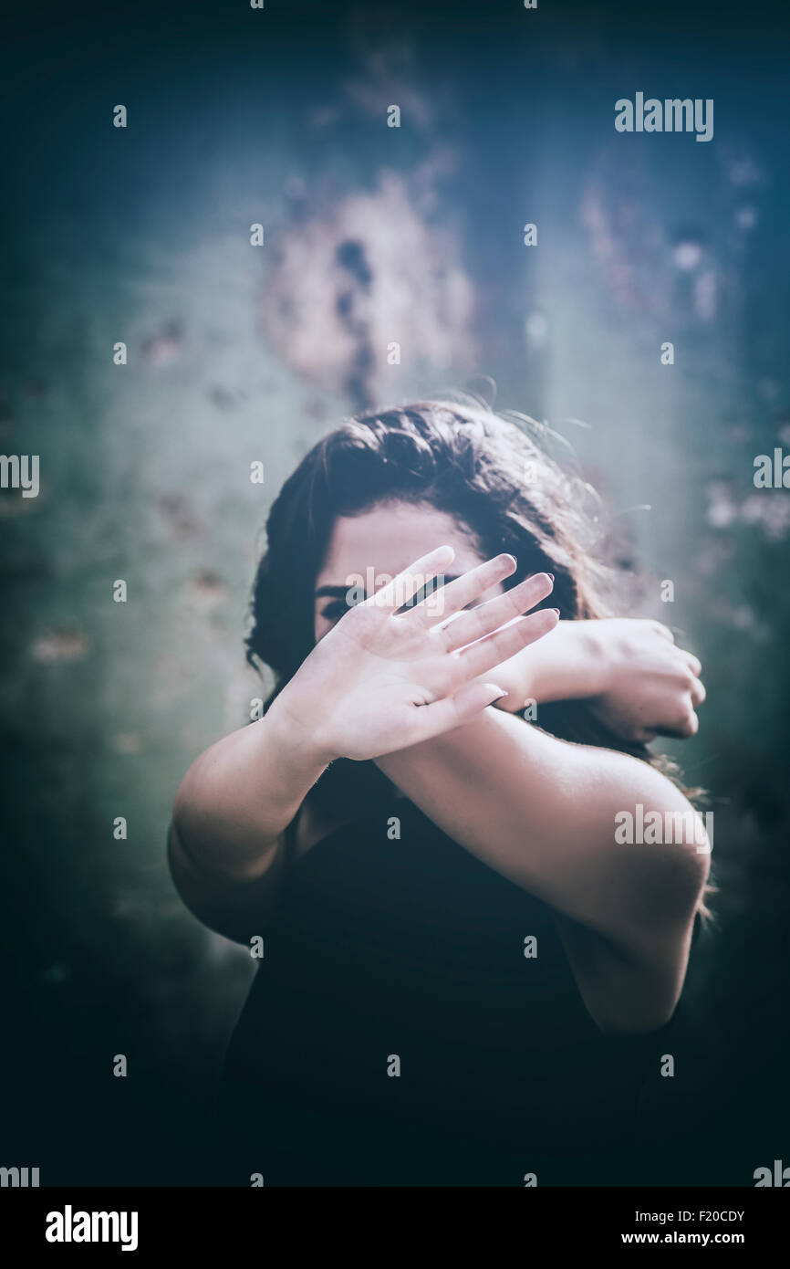 Scared woman hiding face with hands - Stock Image
