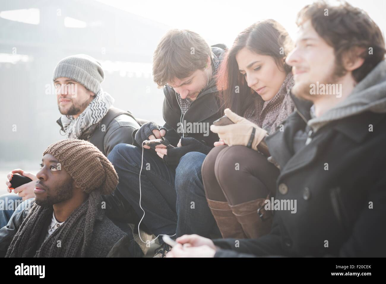 Five young adult friends networking on smartphones - Stock Image