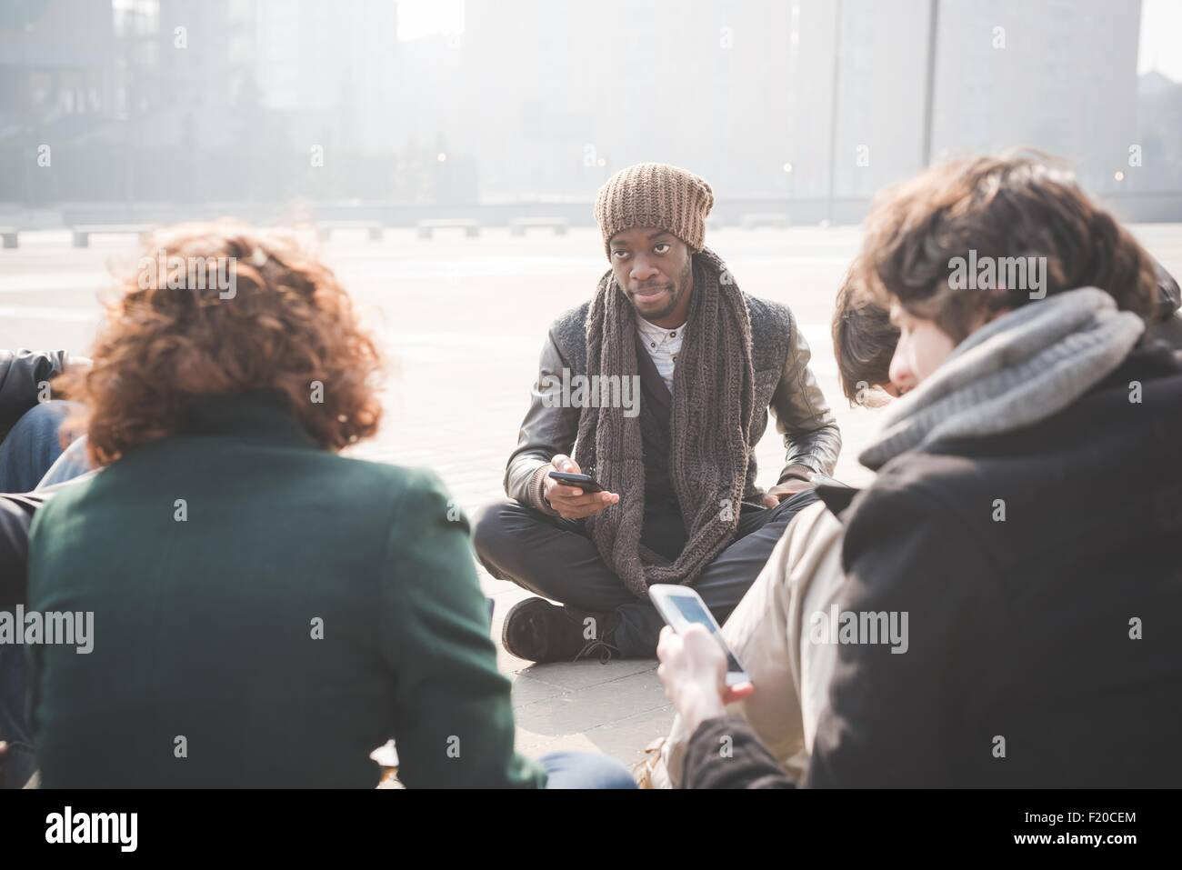 Young adult friends sitting networking on smartphones - Stock Image
