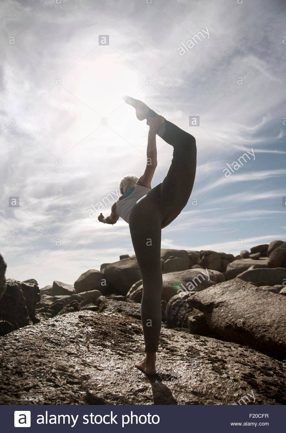 Woman practising yoga by ocean, Cape Town, South Africa - Stock Image