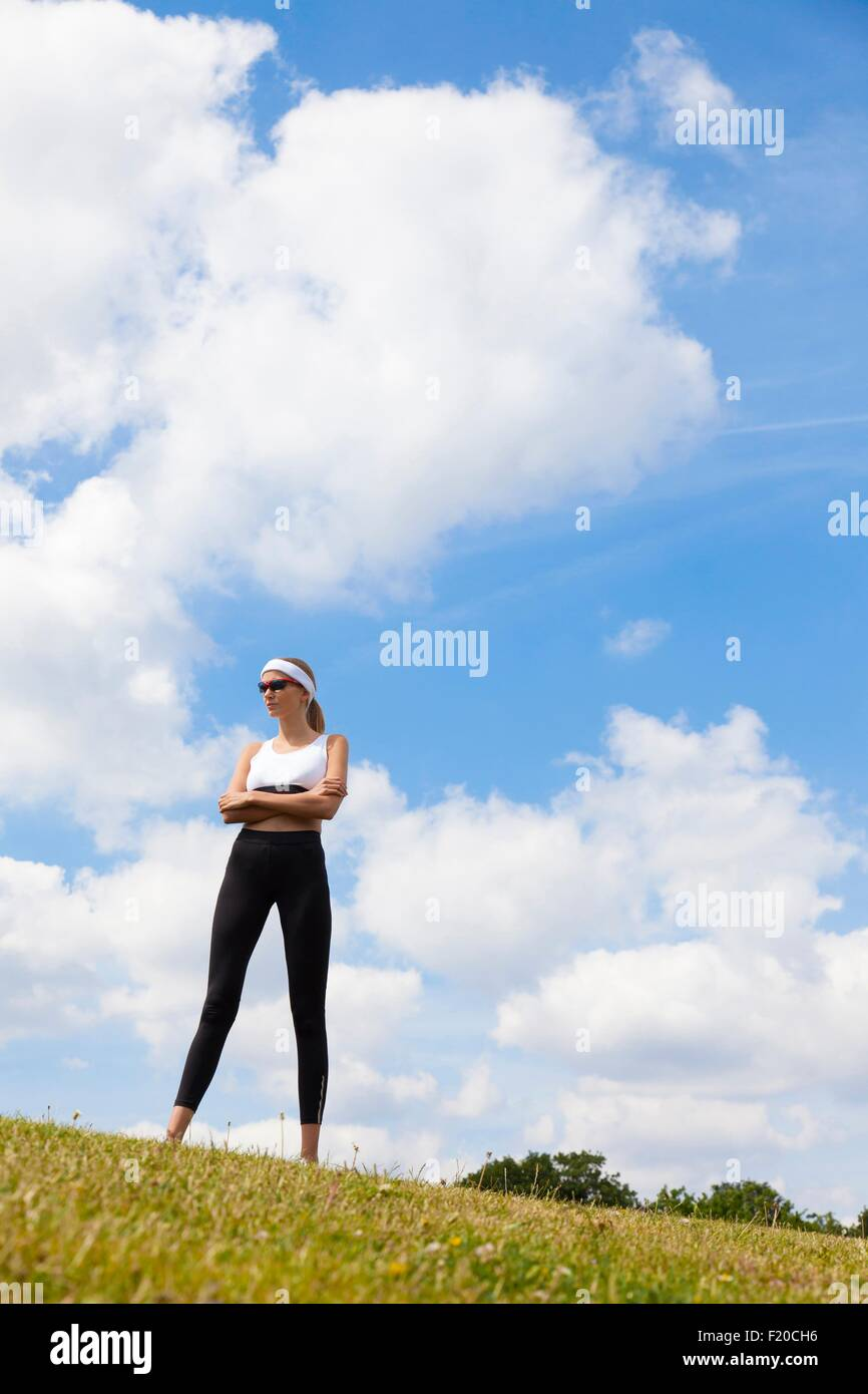 Portrait of jogger against blue skies of countryside - Stock Image