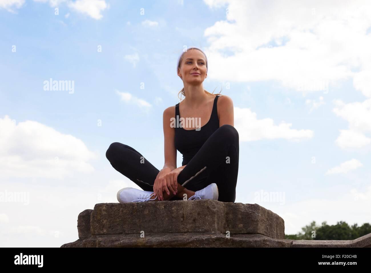 Portrait of woman sitting on pedestal - Stock Image