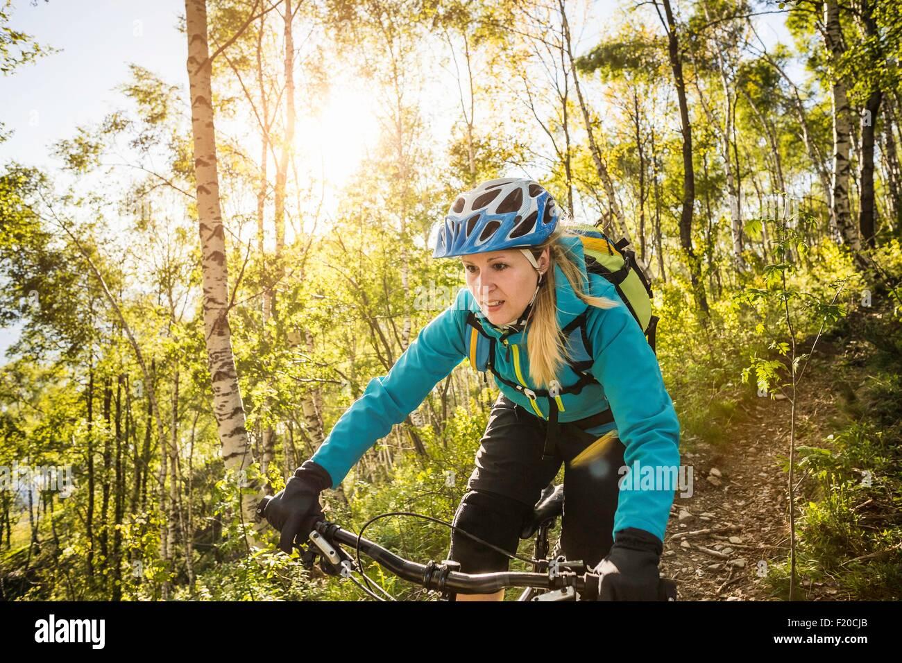 Young woman riding mountain bike through woods, Lake Como, Italy - Stock Image