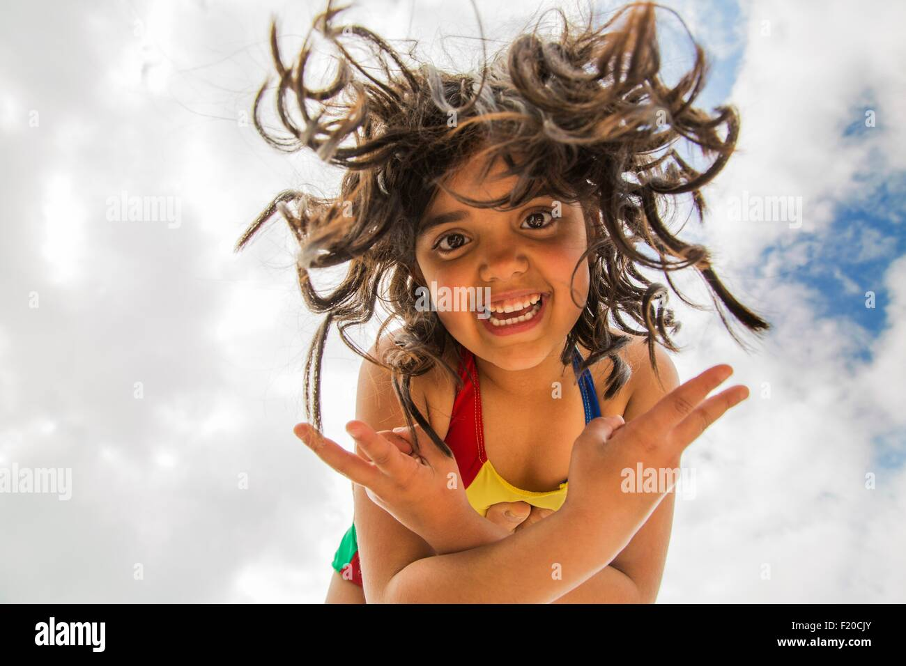 Low angle portrait of girl with long curly hair balancing on top of someones foot - Stock Image
