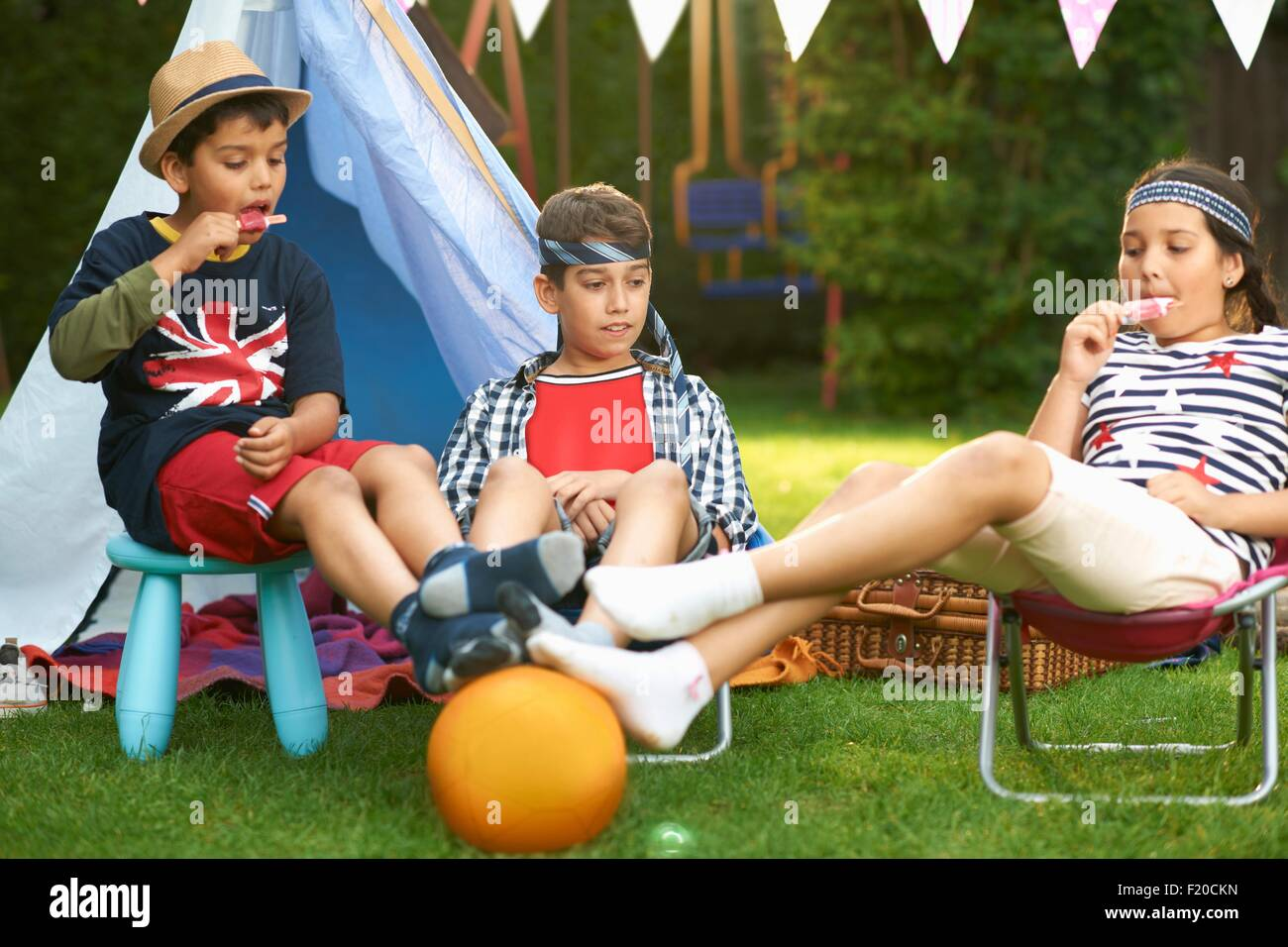 Girl and brothers eating ice lollies in front of homemade tent in garden Stock Photo
