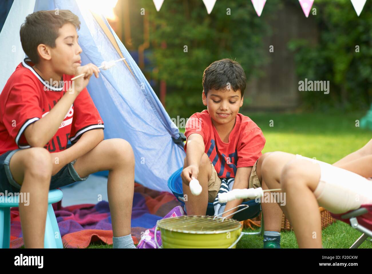 Girl and brothers toasting marshmallows in front of homemade tent in garden - Stock Image