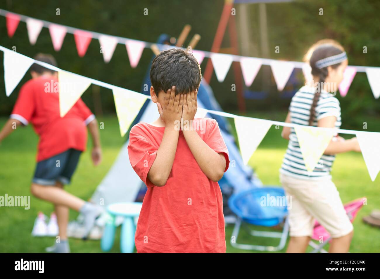 Boy covering his eyes for hide and seek with brother and sister in garden - Stock Image