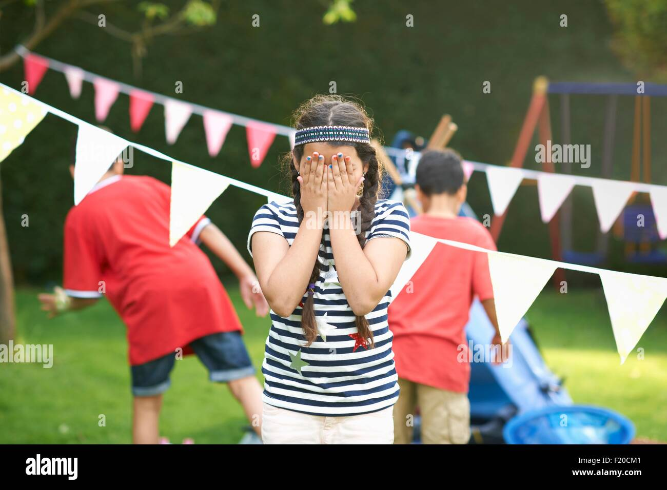 Girl covering her eyes for hide and seek with brothers in garden - Stock Image