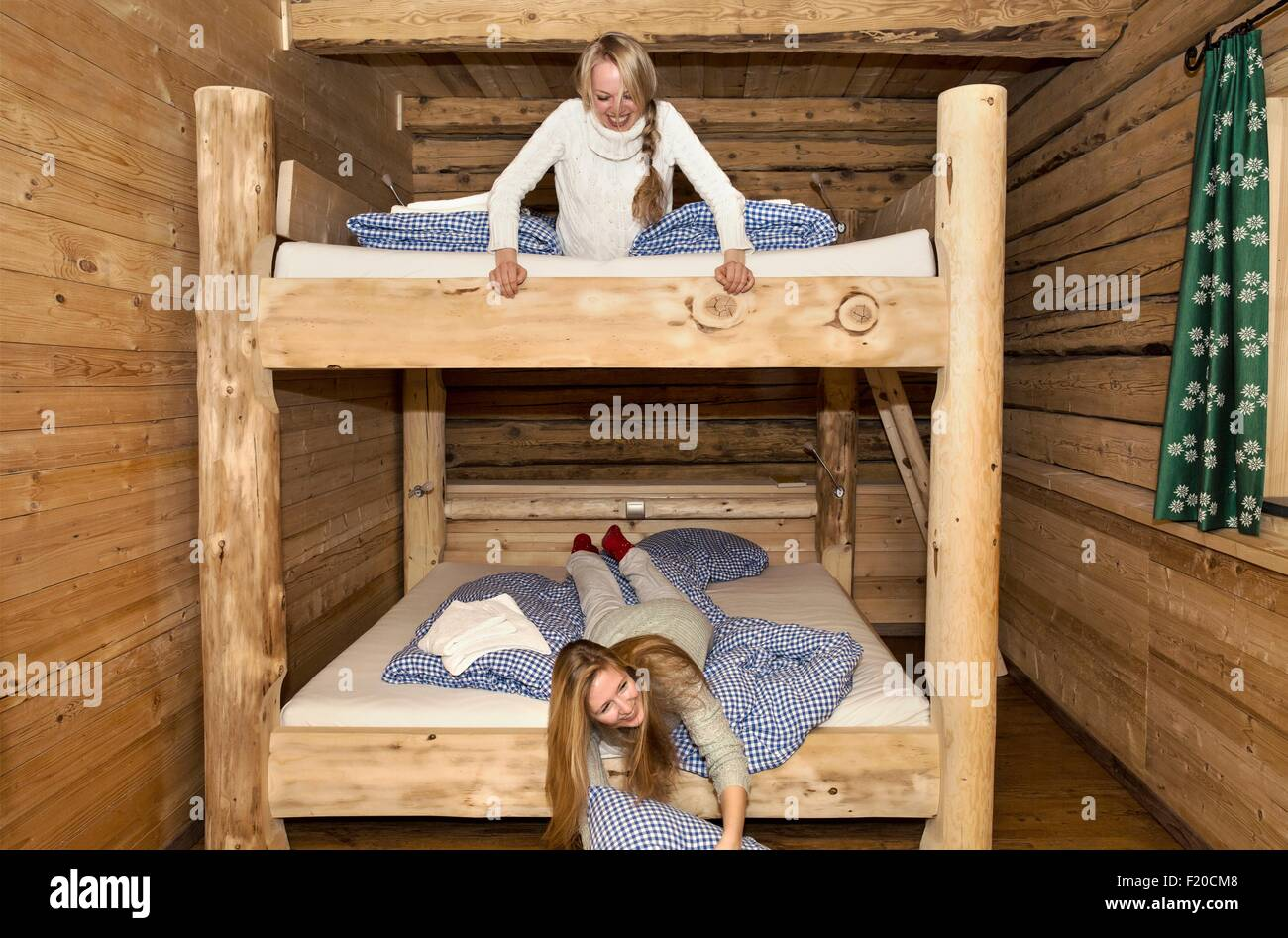 Two young women friends fooling around on bunk beds in log cabin - Stock Image