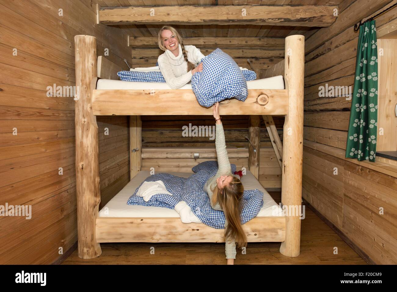 Two young women friends fooling around with pillows on bunk beds in log cabin - Stock Image