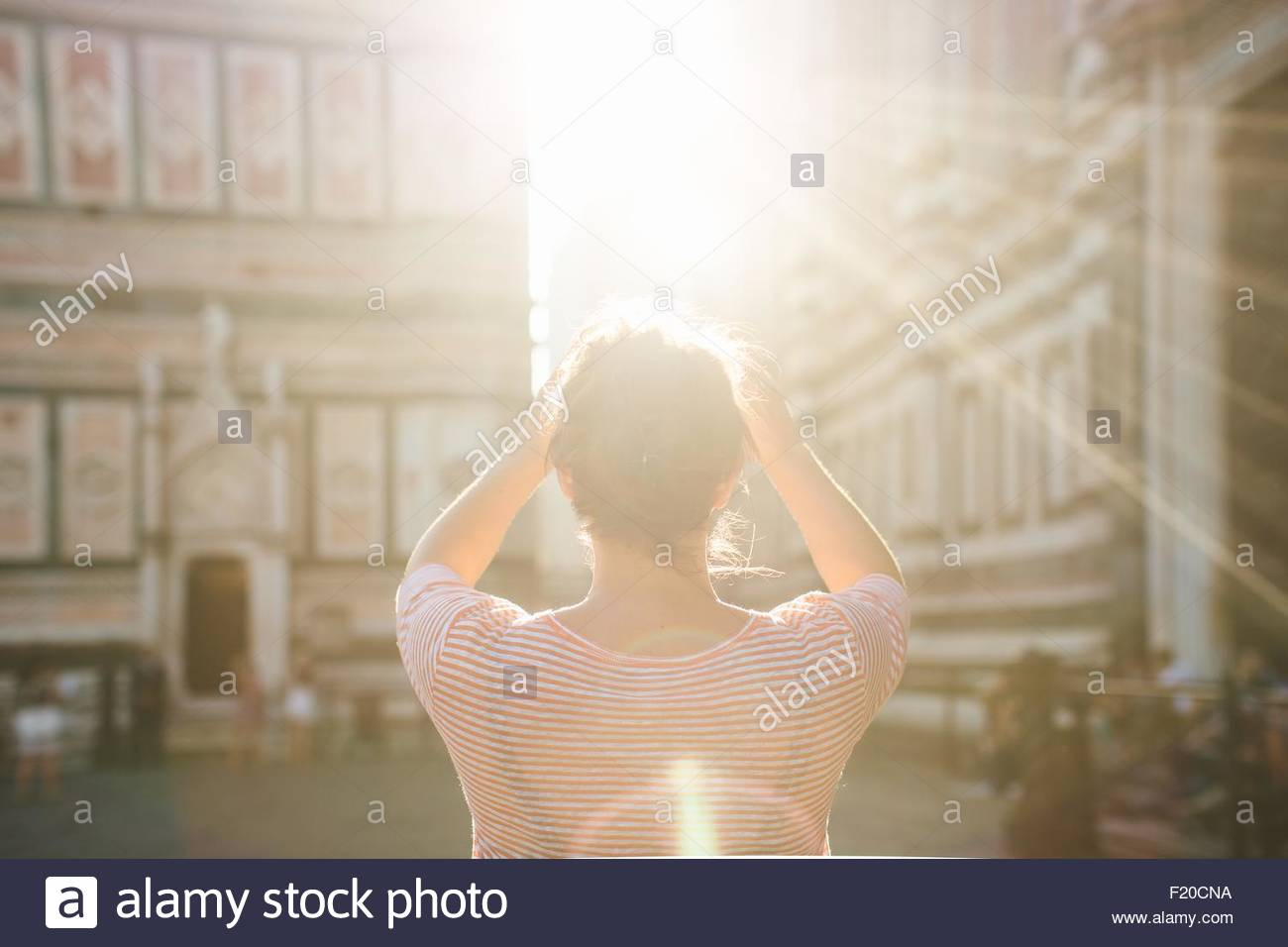 Rear view of mid adult woman, arms raised, lens flare, Duomo Cathedral, Florence, Italy - Stock Image
