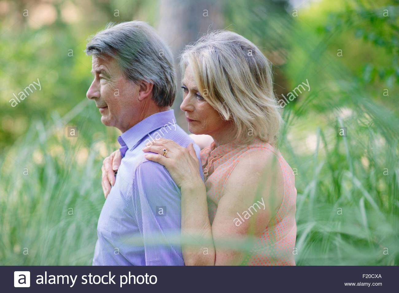 Senior couple standing together, outdoors, with pensive expression - Stock Image