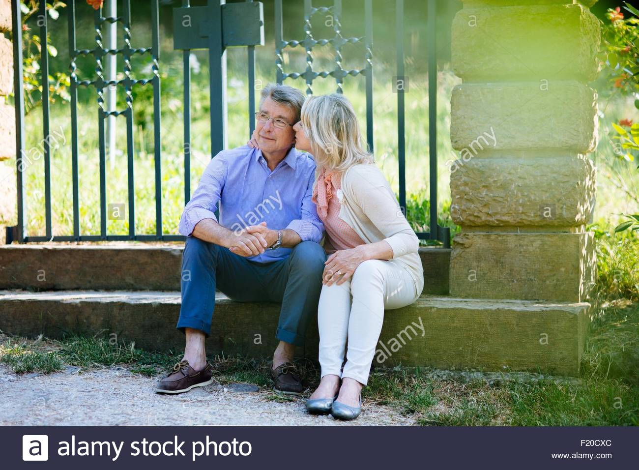 Senior couple sitting on step, woman kissing man's cheek - Stock Image