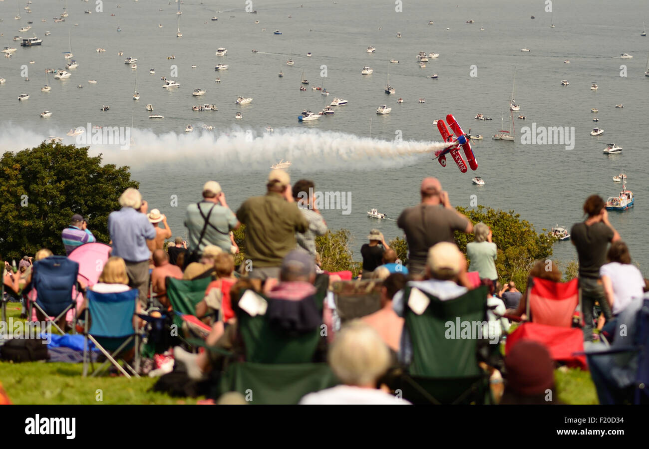 Spectators watching Rich Goodwin's Muscle biplane performing aerobatic fly-past at Dawlish airshow. - Stock Image