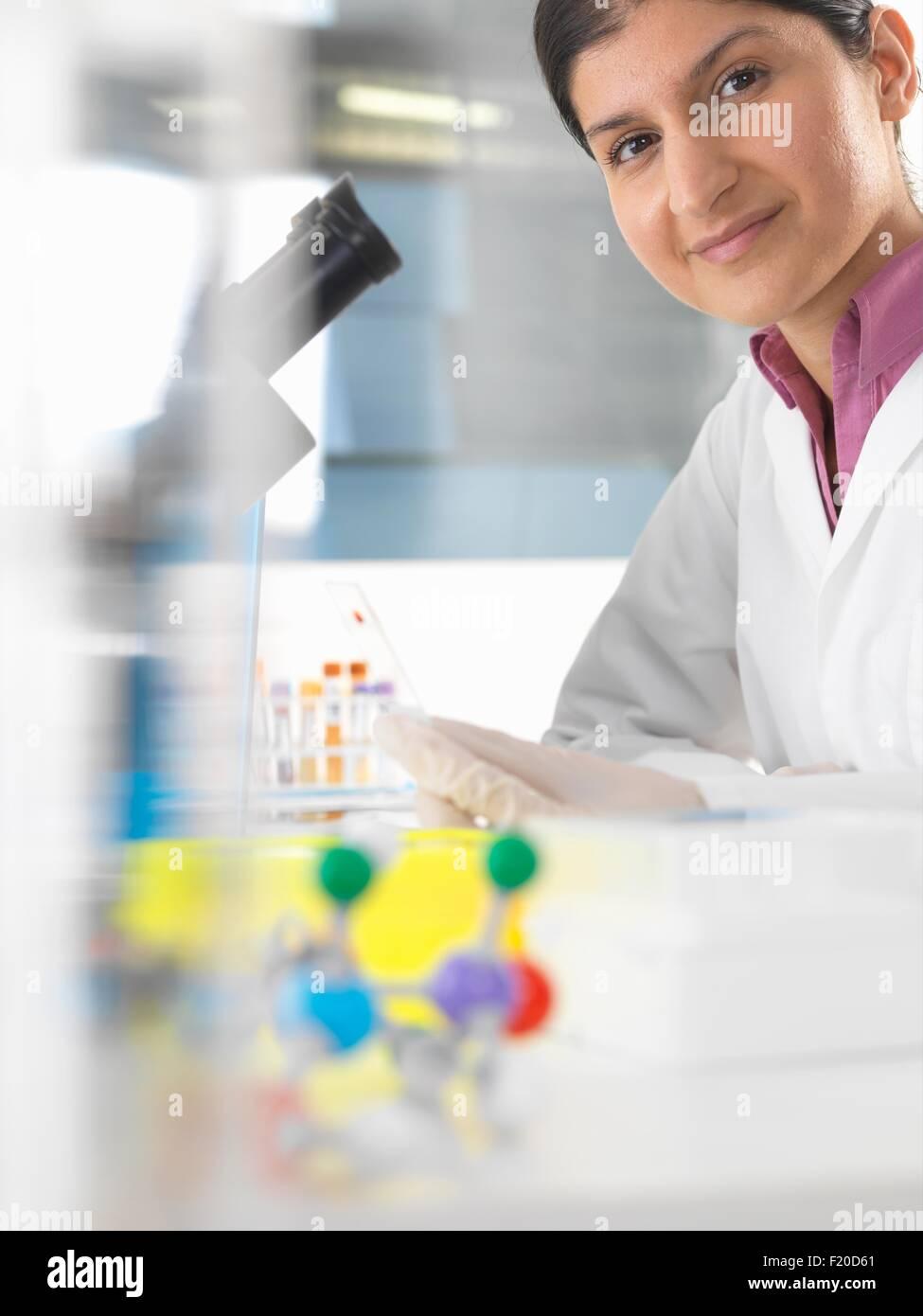 Portrait of female scientist testing blood sample using microscope Stock Photo