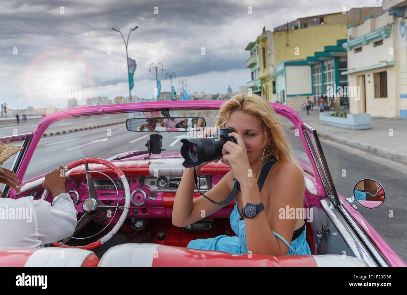Young woman photographing from a vintage car on the Havana' Malecon, Cuba Stock Photo