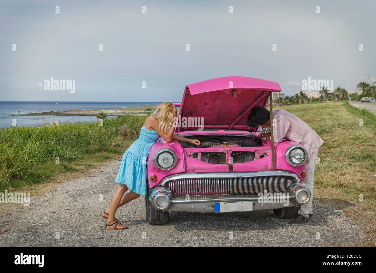 Young couple trying to fix a vintage convertible at coast, Havana, Cuba - Stock Image
