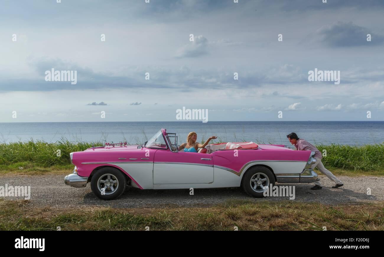 Young man pushing vintage convertible at coast whilst girlfriend drives, Havana, Cuba - Stock Image