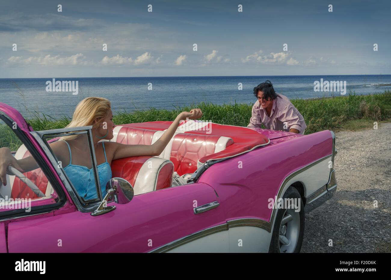 Young man pushing pink vintage convertible at coast whilst girlfriend drives, Havana, Cuba Stock Photo