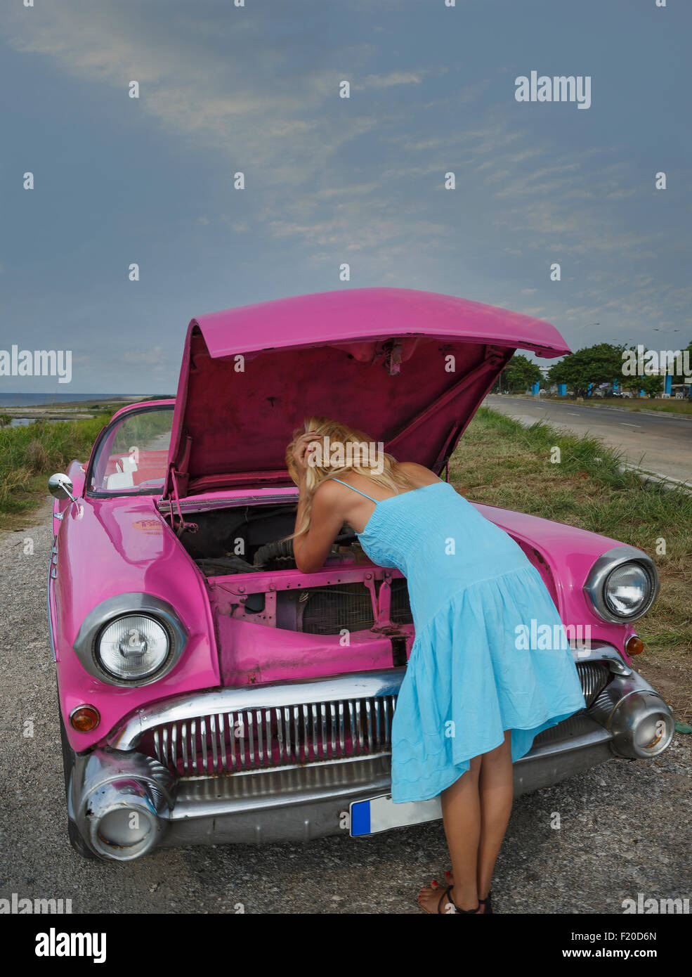 Young woman trying to fix a vintage convertible at coast, Havana, Cuba - Stock Image