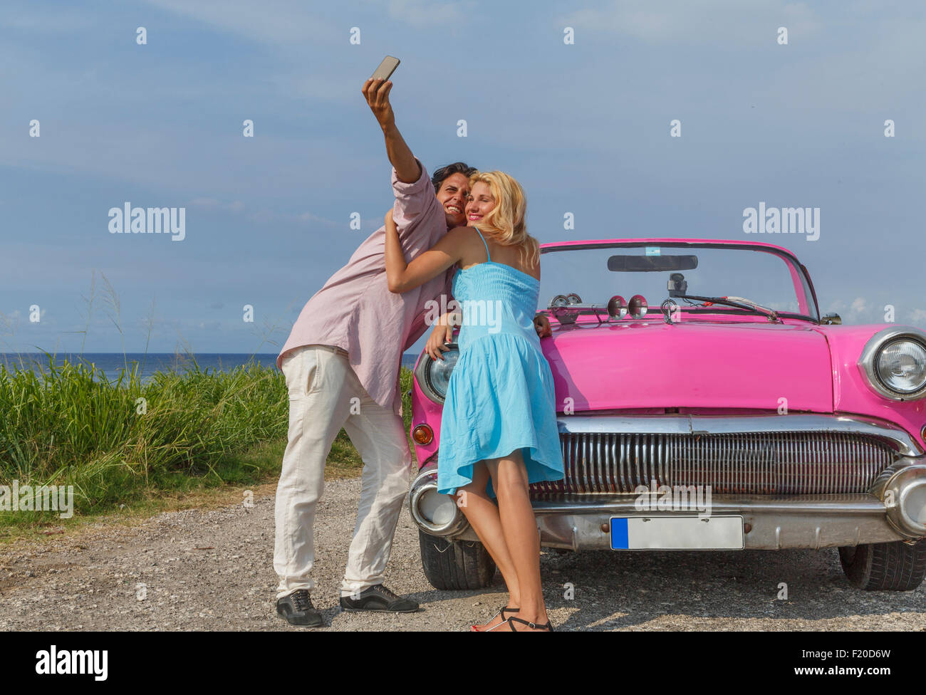 Young couple posing for selfie with vintage convertible, Havana, Cuba - Stock Image