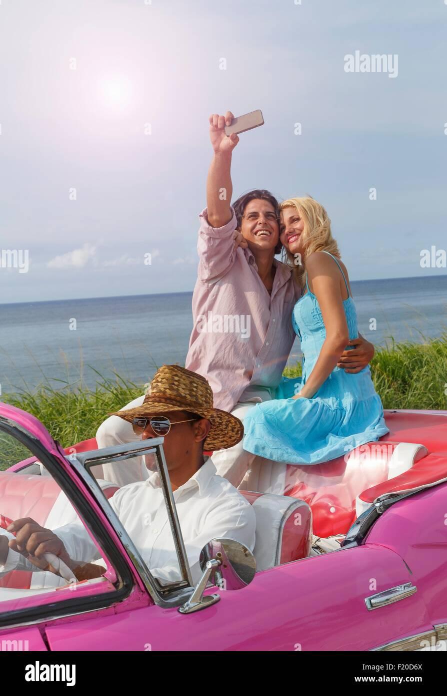 Young couple taking smartphone selfie in vintage convertible, Havana, Cuba Stock Photo