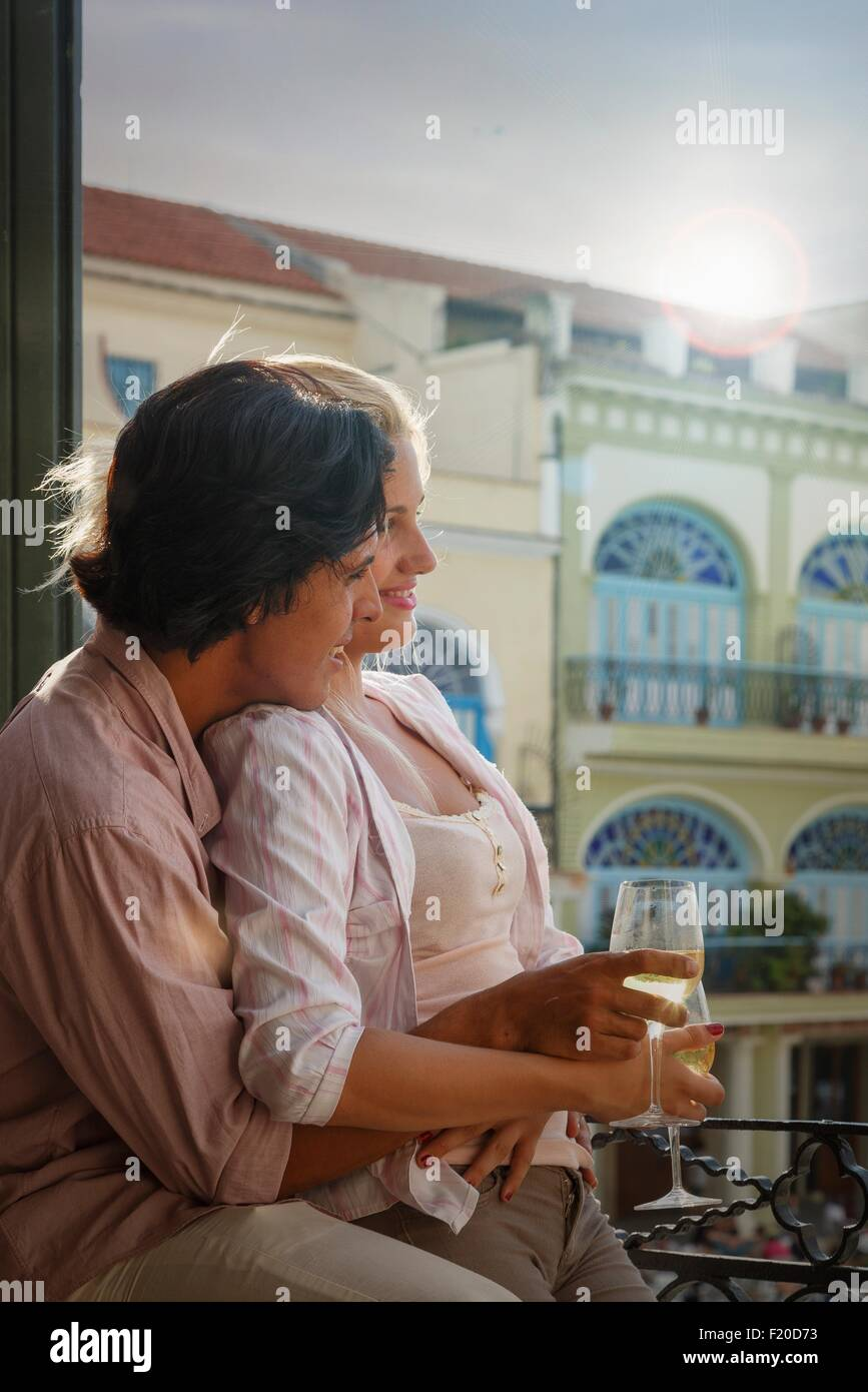 Young couple drinking wine on restaurant balcony in Plaza Vieja, Havana, Cuba - Stock Image