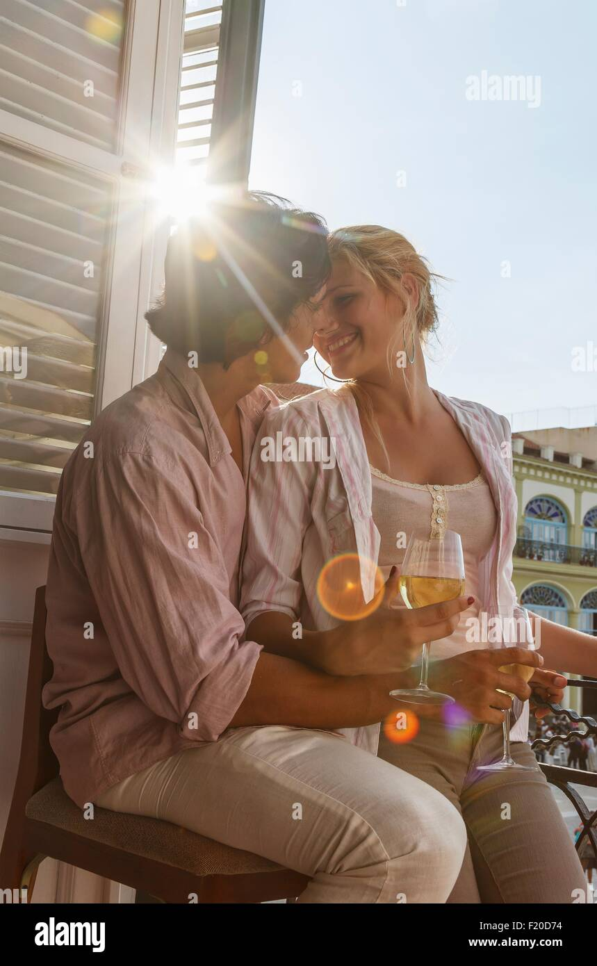 Romantic young couple drinking wine on restaurant balcony in Plaza Vieja, Havana, Cuba - Stock Image
