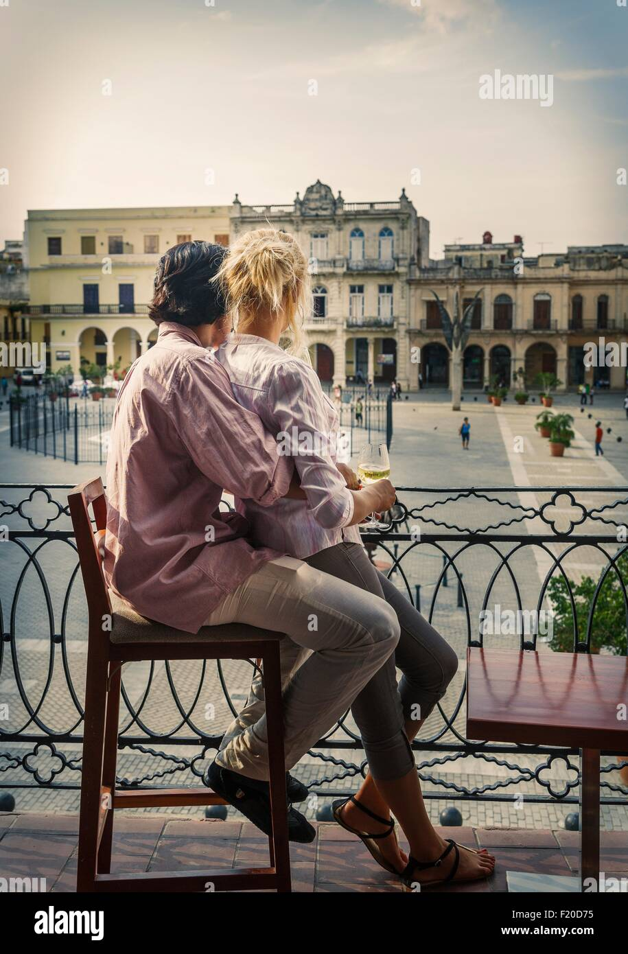 Romantic young couple looking out from restaurant balcony in Plaza Vieja, Havana, Cuba - Stock Image