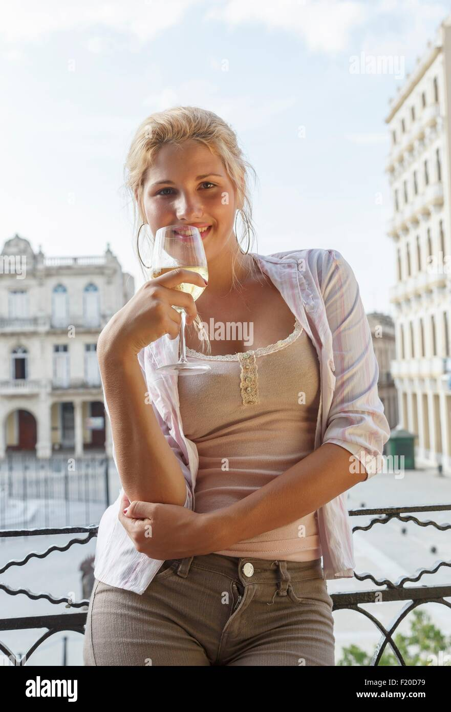 Portrait of young woman drinking wine on restaurant balcony in Plaza Vieja, Havana, Cuba - Stock Image