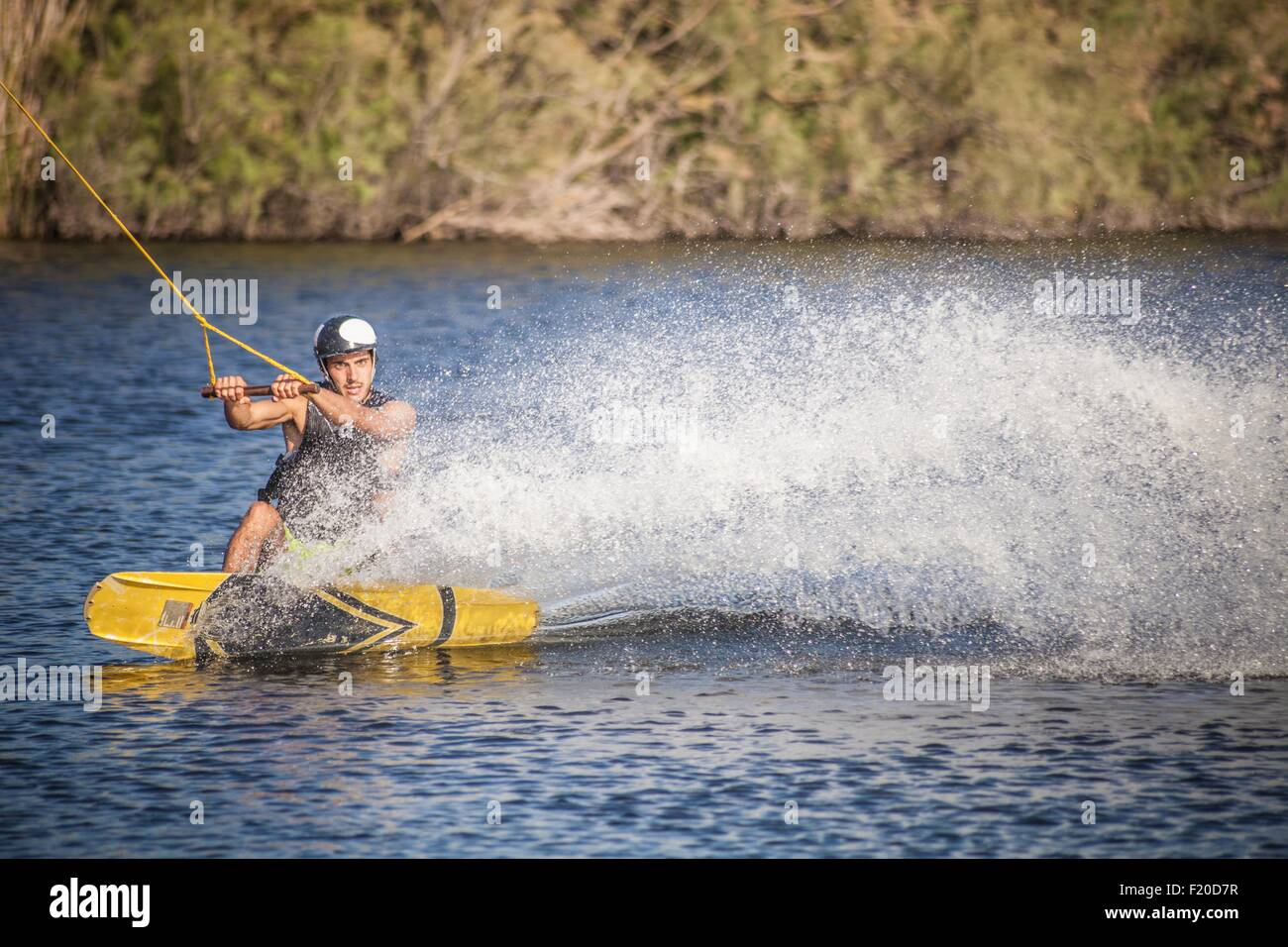 Mid adult man wakeboarding in sea, Cagliari, Sardinia, Italy - Stock Image