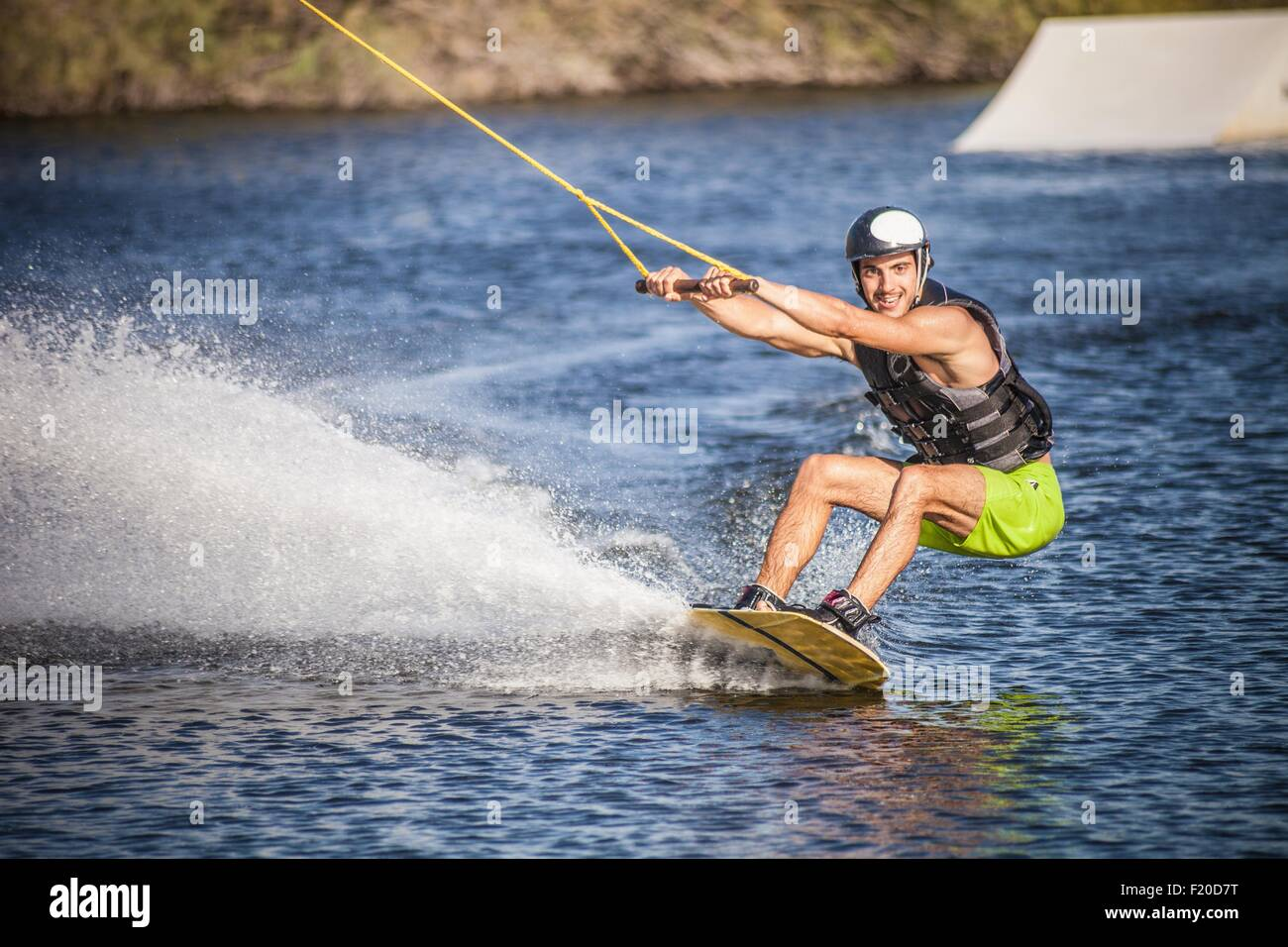 Mid adult man swerving on wakeboard in sea, Cagliari, Sardinia, Italy - Stock Image